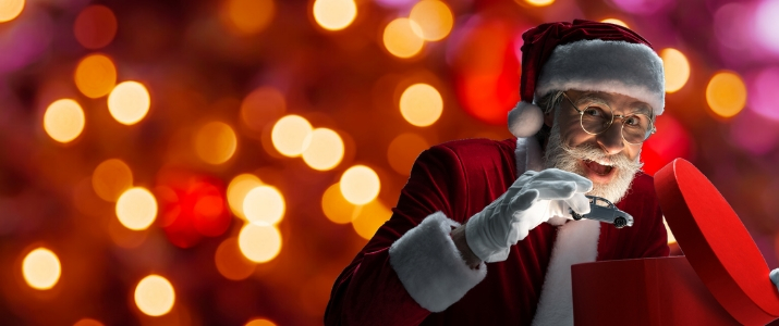 Santa putting a toy car into a gift box on a brightly colored background